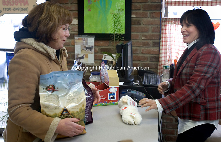 WATERTOWN, CT. 28 January 2011-012811SV10--From left, Judy Connelly of Watertown buys some dog food from Lisa Benemrito at Bone Appetite in Watertown Friday. Sisters Denise Benemrito Garassino and Lisa are the daughters of the owners of Crestwood Ford in Watertown. When that dealership was closed the sisters decided to strike out on a new business path. They opened Bone Appetite, a natural pet food store and boutique.<br /> Steven Valenti Republican-American