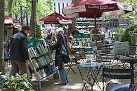 Visitors browse the selection of books on carts at the Reading Room, an open air library in New York City's Bryant Park, behind the New York Public Library.
