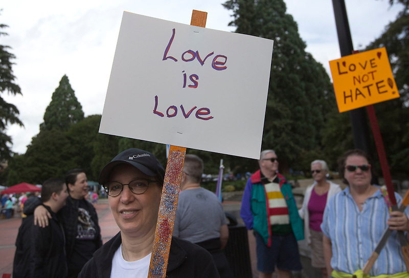 "A woman holds a sign at the ""Dyke March"" part of the Pride event Esther Short Park in downtown Vancouver Sunday July 9, 2016. he annual Saturday in the Park Pride event celebrates the local gay, lesbian, bisexual and transgender community. (Photo by Natalie Behring/ for the The Columbian)"