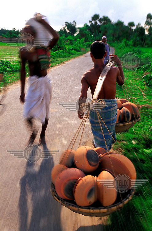 Itinerant pot salesman walking between villages in rural west Bangladesh.  The clay pots are used mainly by rice farming families for storage purposes.