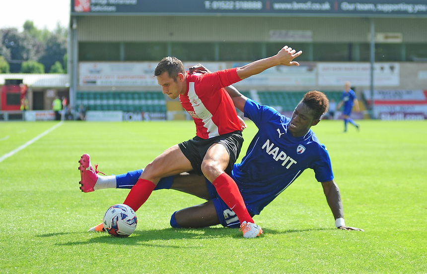 Lincoln City's Ben Tomlinson is tackled by Chesterfield's Armand Gnawduellet<br /> <br /> Photographer Chris Vaughan/CameraSport<br /> <br /> Football - Friendly - Lincoln City v Chesterfield - Saturday 19th July 2014 - Sincil Bank Stadium - Lincoln<br /> <br /> &copy; CameraSport - 43 Linden Ave. Countesthorpe. Leicester. England. LE8 5PG - Tel: +44 (0) 116 277 4147 - admin@camerasport.com - www.camerasport.com