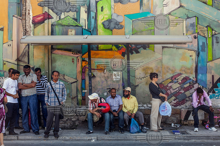 A group of immigrants wait for the bus near a flea market.