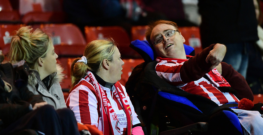 Lincoln City fans watch their team in action<br /> <br /> Photographer Chris Vaughan/CameraSport<br /> <br /> The EFL Checkatrade Trophy Fourth Round - Lincoln City v Peterborough United - Tuesday 23rd January 2018 - Sincil Bank - Lincoln<br />  <br /> World Copyright &copy; 2018 CameraSport. All rights reserved. 43 Linden Ave. Countesthorpe. Leicester. England. LE8 5PG - Tel: +44 (0) 116 277 4147 - admin@camerasport.com - www.camerasport.com