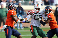 Oct 30, 2010; Charlottesville, VA, USA;   Virginia Cavaliers safety Corey Mosley (7) intercepts the ball in front of Miami Hurricanes wide receiver Leonard Hankerson (85) and Virginia Cavaliers safety Rodney McLeod (4) during the game at Scott Stadium. Virginia won 24-19. Mandatory Credit: Andrew Shurtleff