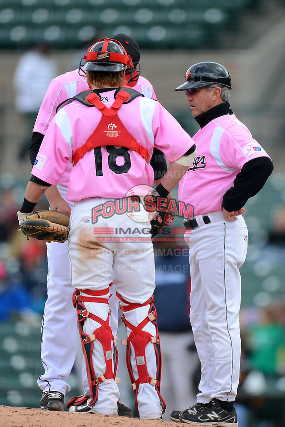 Rochester Red Wings manger Gene Glynn #8 talks with pitcher Daniel Turpen #53 and catcher Chris Herrmann #18 during a game against the Columbus Clippers on May 12, 2013 at Frontier Field in Rochester, New York.  Rochester defeated Columbus 5-4 wearing special pink jerseys for Mother's Day.  (Mike Janes/Four Seam Images)