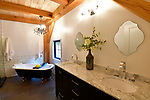 The master bathroom at the home of Steve and Jennifer Schatz of rural Pacific. The open-concept home is designed to resemble a Missouri dairy barn with exposed timbers throughout the interior. The claw-foot tub is opposite a shower. <br /> Photo by Tim Vizer
