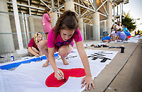 NWA Democrat-Gazette/JASON IVESTER <br /> Rogers High junior cheerleader Jennifer Andrews helps paint spirit sheet signs on Wednesday, Aug. 12, 2015, outside the school's football stadium. Members of the cheer squad painted the signs to hang inside the stadium for the upcoming season.