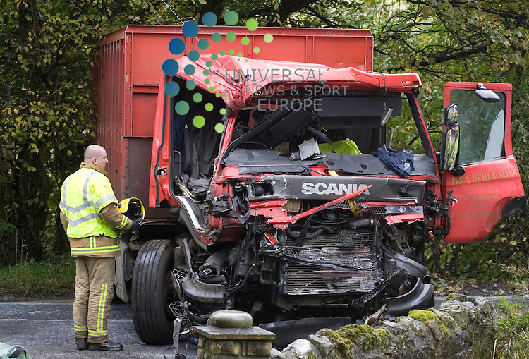 Strathclyde firefighters and traffic police look at the burned out wreckage of two truck s after a lorry carrying milk crashed head on into a farm truck on the Lochwinnoch B786, Renfrewshire. Picture: Universal News And Sport (Scotland).  2 October 2009... .