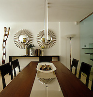 A modern Perspex light hangs over the dining room table and a matching pair of convex mirrors hangs on the wall
