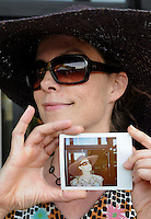 Holly Deye holds a Polaroid photo depicting the wide brim hat and sunglasses she wore to the 2011 Bumbershoot music and arts festival in Seattle Center on Monday, September 5, 2011. Deye said she purchased the hat while walking through the Ballard Seafood Fest a few years ago.