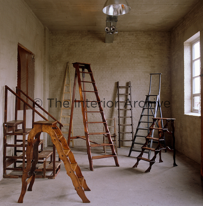 A collecton of antique library ladders is displayed in an industrial space