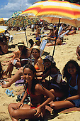 Salvador, Brazil. Beach scene; smiling family on the beach with sunshades.