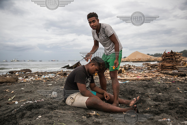 Bartholomew Kokolopu, 18, cutting the hairof  his friend, <br /> Eddiemurphy Kabui, 18, hair on a beach in Lord Howe Settlement. Bartholomew says: 'I was born here, Eddiemurphy was born on Ongoing Java. But we both feel home here in the Settlement, despite that everyone here, including us, calls the atoll 'home.'<br /> Lord Howe Settlement, a district of the capital Honaria, is populated by people from Ontong Java Atoll (AKA Lord Howe Atoll), a Polynesian outlier of the Solomon Islands. Its people have been moving to Lord Howe Settlement in search of a better life since the 1970s. Climate change leading to rising sea levels and consequent food insecurity now means the atoll is existentially threatened. The remaining Ontong Javanese people are considering the possibility of complete relocation to Santa Isabel Island and to Honiara. However, with Lord Howe Settlement itself suffering the consequences of extreme weather and overcrowding, community leaders believe it is not a viable long term home. Furthermore, they fear that the Ontong Javanese people's Polynesian identity will be lost as a new generation is brought up in a location with no connection to ancestral land. Their identity will be weakened as they become a minority amongst Melanesian communities that have vastly different traditions and speak different languages.