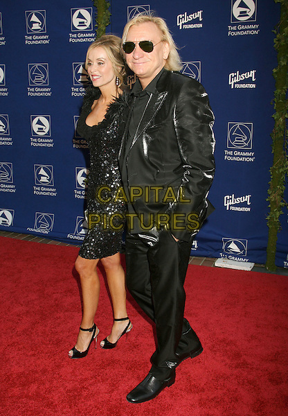 """JUANITA & JOEL WALSH.""""Starry Night"""" Grammy Foundation Benefit In Honor Of Sir George Martin held at the University Of Southern California, USA, Los Angeles, California, USA, 12th July 2008..full length black dress suit jacket shiny sunglasses boots married husband wife .CAP/ADM/MJ.©Michael Jade/Admedia/Capital Pictures"""