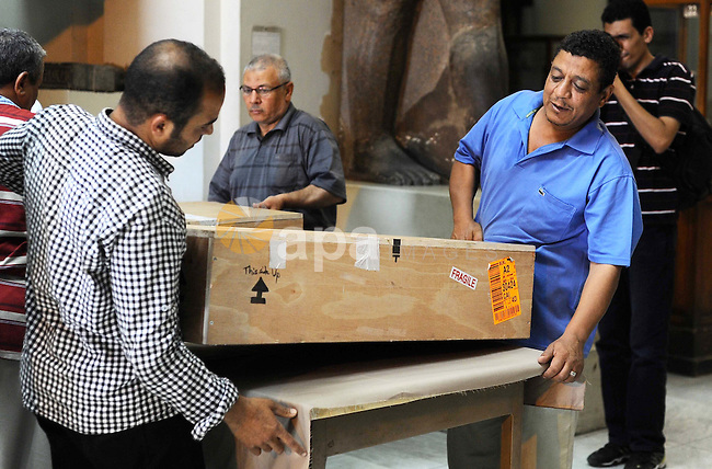 Egyptian antiquities officials carry a lid of a sarcophagus on its arrival to the Egyptian Museum in Cairo, Egypt, on June 21, 2016. Two ancient Egyptian sarcophagus covers have been delivered to Cairo's Egyptian Museum after they surfaced at an auction in Israel. Antiquities Minister Khaled el-Anani says the colorful wooden covers, decorated with hieroglyphics and illustrations, were recovered after they went on sale in 2012 and returned following cooperation between the two countries and Interpol. Photo by Amr Sayed