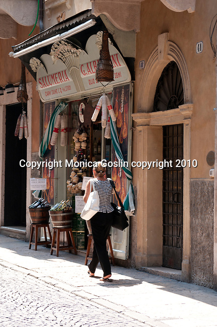 A woman walks by a deli in Verona, Italy.