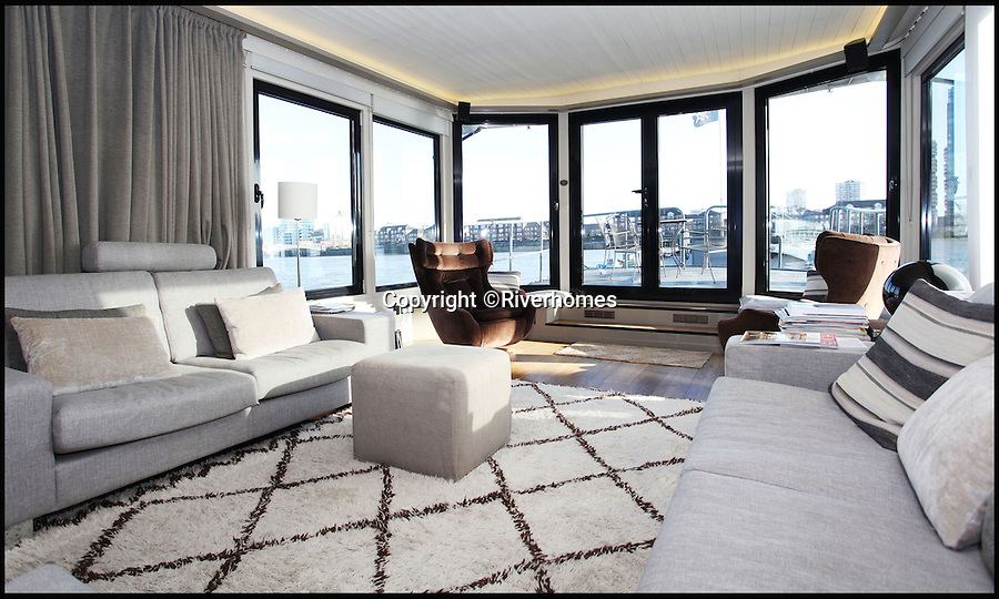 BNPS.co.uk (01202 558833)<br /> Pic: Riverhomes/BNPS<br /> <br /> Luxurious lounge.<br /> <br /> Heart of Lightness - Tardis like houseboat on the Thames.<br /> <br /> A houseboat that looks more like a luxurious penthouse suite inside has gone on the market for a whopping £1.5 million - because it's in one of London's most exclusive locations.<br /> <br /> The 100ft vessel was once a former Dutch barge taking supplies up and down the Thames until it was retired from service in the 1960s and left to rot.<br /> <br /> But a decade later it was salvaged and turned into a houseboat before undergoing a complete refurbishment four years ago and moved to a premier mooring alongside one the swankiest addresses in the city.<br /> <br /> The plush houseboat, berthed at the entrance to Cheyne Walk, now boasts a lavish living room, stylish 50ft-long kitchen, a spiral staircase, two opulent bedrooms, three bathrooms and even a sun terrace.<br /> <br /> And despite its eye-watering £1.5m asking price, experts at Riverhomes estate agents say the houseboat is actually a bargain and that anyone wanting to live in such luxury in the heart of Chelsea would have to shell out many millions more.