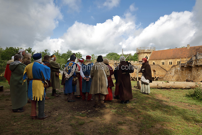 Visitors on a tour, dressed in medieval costume, at the Chateau de Guedelon, a castle built since 1997 using only medieval materials and processes, photographed in 2017, in Treigny, Yonne, Burgundy, France. The Guedelon project was begun in 1997 by Michel Guyot, owner of the nearby Chateau de Saint-Fargeau, with architect Jacques Moulin. It is an educational and scientific project with the aim of understanding medieval building techniques and the chateau should be completed in the 2020s. Picture by Manuel Cohen