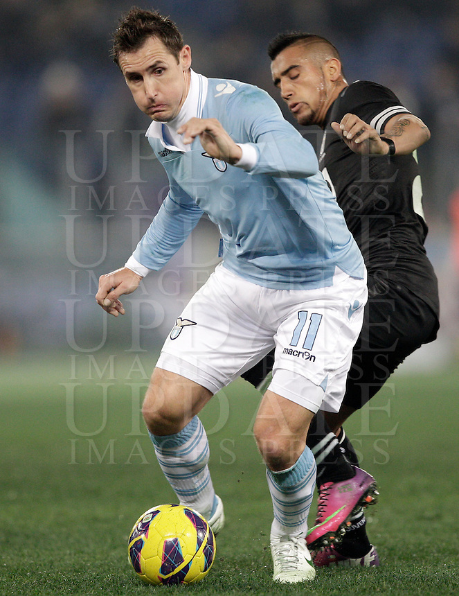 Calcio, semifinale di ritorno di Coppa Italia: Lazio vs Juventus. Roma, stadio Olimpico, 29 gennaio 2013..Lazio forward Miroslav Klose, of Germany, is challenged by Juventus midfielder Arturo Vidal, of Chile, right, during the Italy Cup football semifinal return leg match between Lazio and Juventus at Rome's Olympic stadium, 29 January 2013..UPDATE IMAGES PRESS/Riccardo De Luca