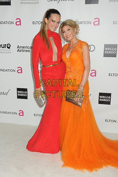 Petra Nemcova, Hofit Golan.20th Annual Elton John Academy Awards Viewing Party held at West Hollywood Park, West Hollywood, California, USA..February 26th, 2012.oscars full length dress one sleeve cut out away gold belt silver clutch bag orange.CAP/ADM/BP.©Byron Purvis/AdMedia/Capital Pictures.