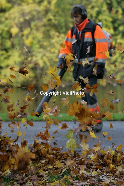 Foto: VidiPhoto..ARNHEM - Om de paden in de Arnhemse parken schoon te houden en ongevallen te voorkomen, zijn medewerkers van Eemfors Groenvoorziening uit Amersfoort donderdag aan het werk in het park achter Musis Sacrum. Het verwijderen van herfstbladeren is op dit moment een dagtaak. Eemfors BV biedt werk aan 400 mensen. Een deel van de medewerkers heeft een psychische, verstandelijke of lichamelijke beperking.