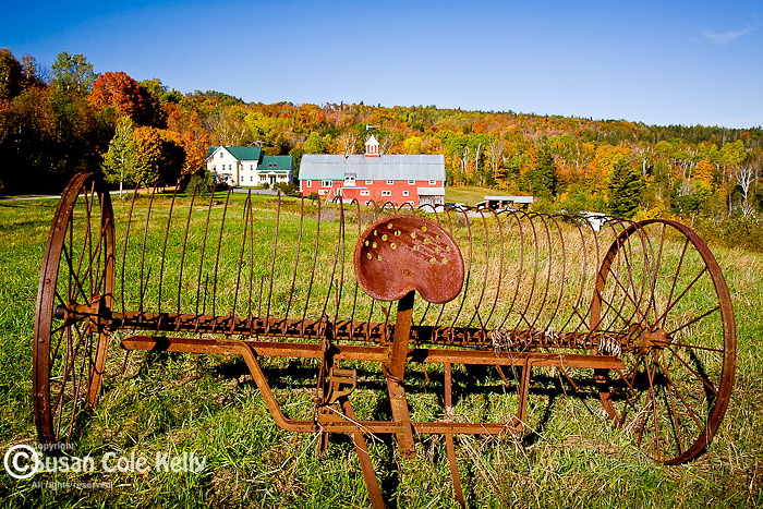 An old farm implement and a red barn in autumn, Danville, VT, USA