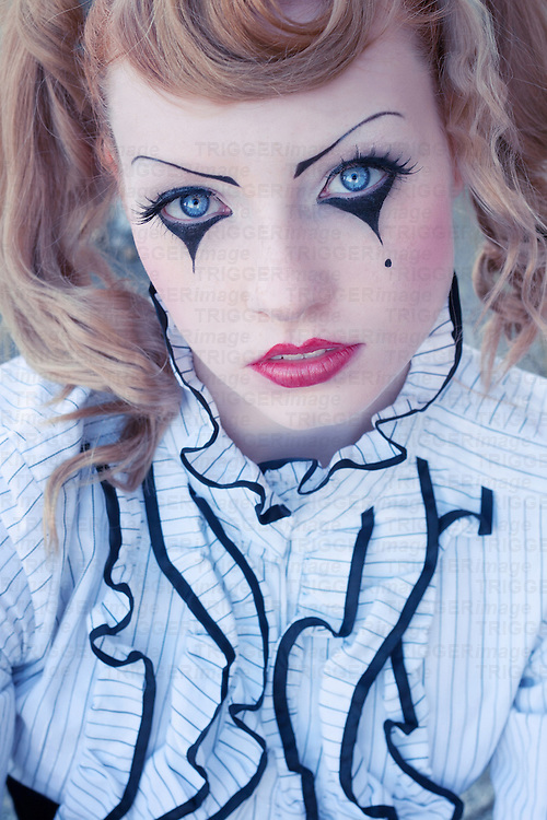 Young red head female  with clown make-up on eyes