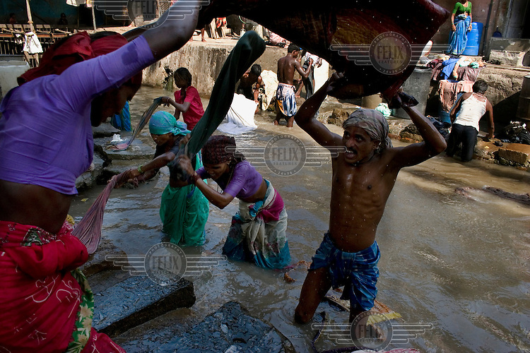 Venkatesh Dhobi (of the Dalit washer caste) washing clothes in the dirty sewage water of the Dharavi ghat. His four children work with him, and they are the fifth generation of his family to work in this pool. Together, Mr Dhobi, his wife and children earn less than 200 rupees a day.