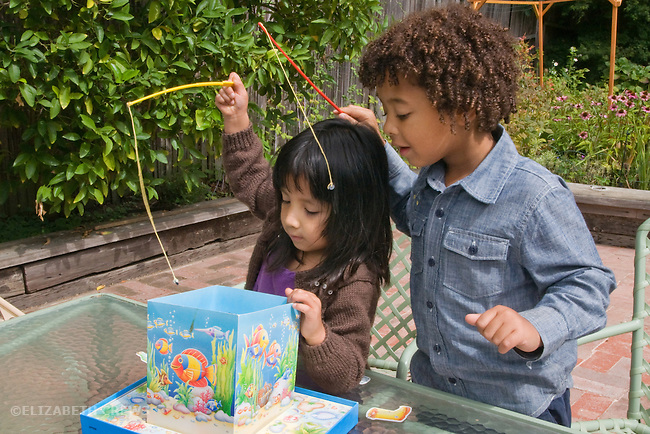 erkeley CA Girl, four,  adopted Guatemalan, playing fishing game with boy cousin, five, half African American  MR