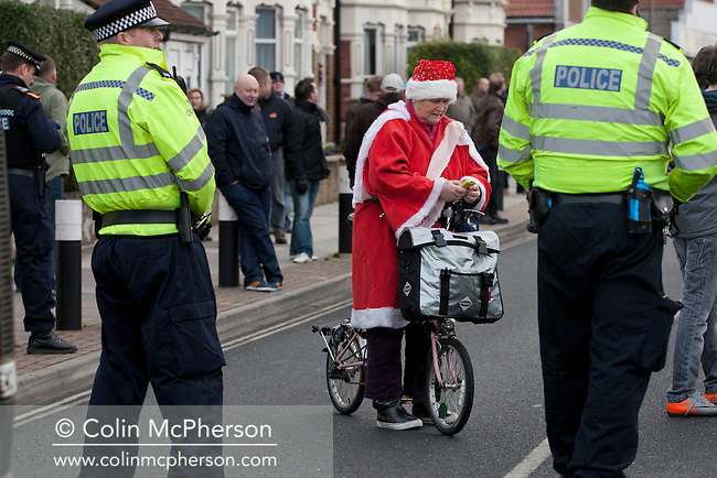 """A woman on a bicycle dressed in a Father Christmas suit waiting to cross a line of police officers in a closed-off street outside Fratton Park stadium before Portsmouth take on local rivals Southampton in a Championship fixture. Around 3000 away fans were taken directly to the game in a fleet of buses in a police operation known as the """"coach bubble"""" to avoid the possibility of disorder between rival fans. The match ended in a one-all draw watched by a near capacity crowd of 19,879."""