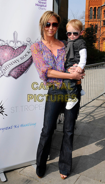 "JENNY FROST & SON CASPER.At the 2nd ""Mummy Rocks"" Fundraising event, The Tabemrche, powis Square, London, England, UK, March 21st 2009..full length sunglasses purple print top blouse wide leg jeans dummy pacifier baby carrying .CAP/CAN.©Can Nguyen/Capital Pictures"