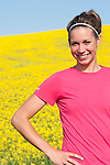 Healthy young woman runner smiling at the camera in front of a field of yellow canola Manitoba, Canada