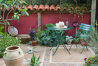 Mediterranean style garden courtyard patio with terracotta roof tile fence, urns, garden furniture, herbs, shrubs, flowers, plants in a dry drought tolerant garden, outdoor lifestyle, book, hat, coffee drinking, peaceful secluded backyard spot, green bistro set