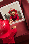18 month old toddler boy wearing play fire hat pointing to reflection of self in mirror, recognizing self
