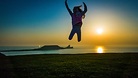 WEATHER PICTURE WALES<br /> A young girl jumps in the air as the sun sets over Worms Head at the end of a warm sunny day in Rhossili, Gower Peninsula, Wales, UK.