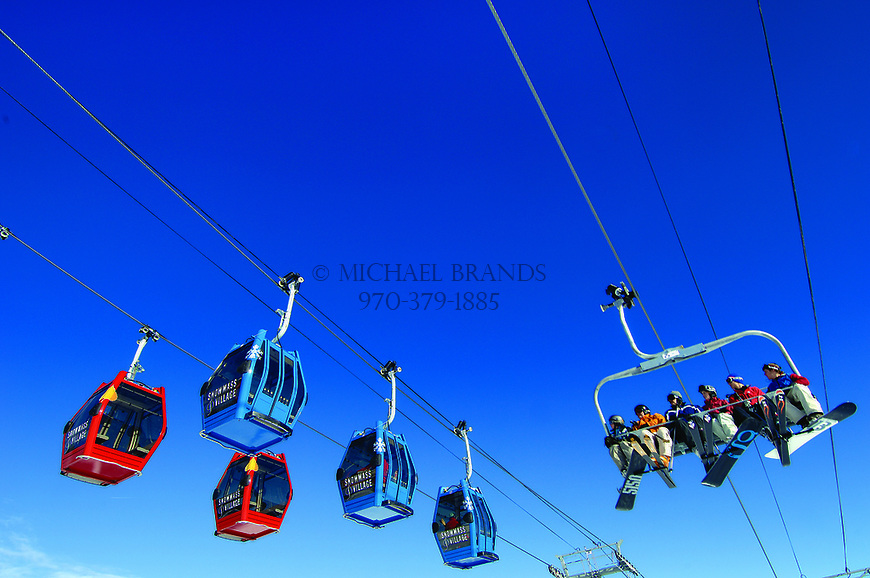 Skiers and snowboarders ride a chair lift at Snowmass ski area, near Aspen, Colorado. © Michael Brands. 970-379-1885.