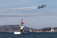 Blue Angels F-18 Hornets in diamond formation pass over the Coast Guard Cutter Pike (WPB-87365) during a 2019 San Francisco Fleet Week flight demonstration.