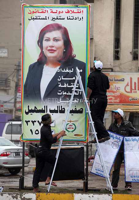 BAGHDAD, IRAQ: Workmen put up elections posters in the lead up to the March 7th Parliamentary elections in Iraq...Photo by Ceerwan Aziz/Metrography