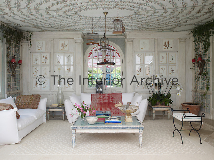 In the orangery 19th century birdcages are suspended from a ceiling hand-painted by Florentine artisans and the walls are decorated with framed dried flowers