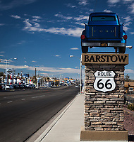 A roadside sign on a city street acknowledging an iconic roadway in American urban history, Route 66, with a classic pickup truck on top under a blue sky and scattered clouds.