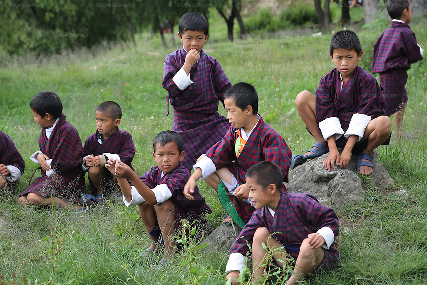 Boys school children at Wangdue Chhoeling Lower Secondary School, Bumthang, Bhutan..Bhutan the country that prides itself on the development of 'Gross National Happiness' rather than GNP. This attitude pervades education, government, proclamations by royalty and politicians alike, and in the daily life of Bhutanese people. Strong adherence and respect for a royal family and Buddhism, mean the people generally follow what they are told and taught. There are of course contradictions between the modern and tradional world more often seen in urban rather than rural contexts. Phallic images of huge penises adorn the traditional homes, surrounded by animal spirits; Gross National Penis. Slow development, and fending off the modern world, television only introduced ten years ago, the lack of intrusive tourism, as tourists need to pay a daily minimum entry of $250, ecotourism for the rich, leaves a relatively unworldly populace, but with very high literacy, good health service and payments to peasants to not kill wild animals, or misuse forest, enables sustainable development and protects the country's natural heritage. Whilst various hydro-electric schemes, cash crops including apples, pull in import revenue, and Bhutan is helped with aid from the international community. Its population is only a meagre 700,000. Indian and Nepalese workers carry out the menial road and construction work.