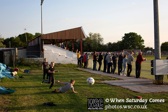 Three young boys playing football on the terrace during the first-half at Yockings Park as Whitchurch Alport hosted Cammell Laird 1907 in the 2017-18 North West Counties Division One play-off final. Alport were formed in 1946 and were named after Alport Farm, Whitchurch, which had been the home of a local footballer Coley Maddocks who had been killed in action in the war. The home team won the match 2-1 watched by a crowd of 733, a club record attendance.