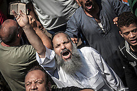 In this Friday, Jul. 05, 2013 photo, a member of the Muslim Brotherhood and supporter of the ousted president Morsi shouts slogans as he holds a printed version of the Quran at the University of Cairo in Giza against the military's coup in Cairo, Egypt. (Photo/Narciso Contreras).