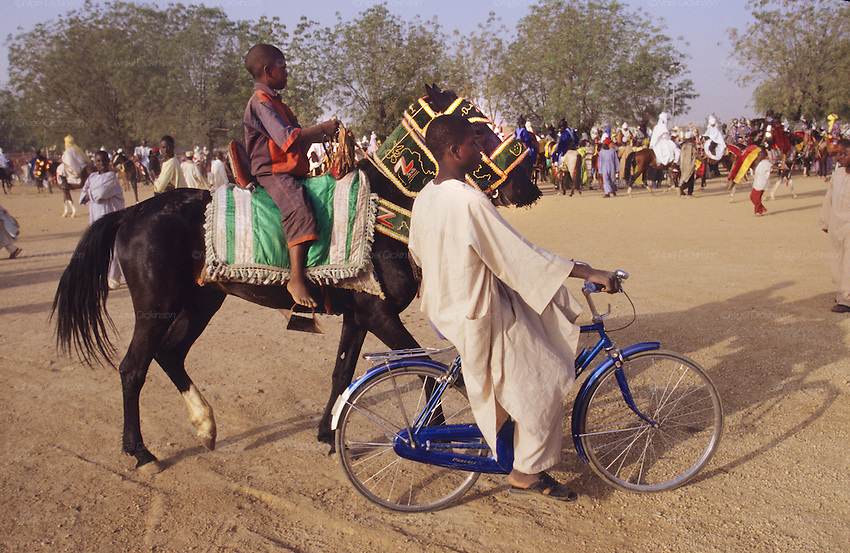 Youth on a horse is lead into the Fantasia park by a member of his family riding a bicycle..The Durbar Fantasia, is the moment where The Husa residents of Kano wear traditional dress, their local leaders and chiefs mount horses, and together with their militias display allegiance and homage to their leader, the Emir of Kano. This takes place after Ramadan. The Emir is Kano's State official political and economic feudal leader, everyone seeks to be in his pleasure, otherwise they reap the consequences..Kano is the largest Muslim Husa city, under the feudal, political and economic rule of the Emir. Kano and the other eleven northern states are under Islamic Sharia Law which is enforced by official state apparatus including military and police, Islamic schools and education, plus various volunteer Militia groups supported financially and politically by the Emir and other business and political bodies. 70% of the population live below the poverty line. Kano, Kano State, Northern Nigeria, Africa