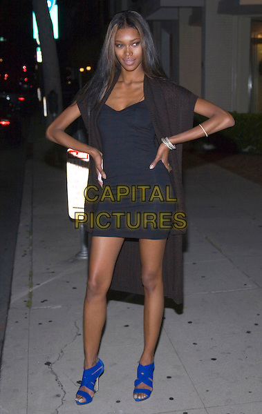 JESSICA WHITE .Sports Illustrated Model Jessica White at Mr. Chow Restaurant in Beverly Hills, California, USA, 2nd June 2009..full length black dress blue wrap knitted cardigan blue sandals hands on hips mini ribs ribcage skinny collar bone bony .CAP/ADM/TC.©T. Conrad/Admedia/Capital Pictures