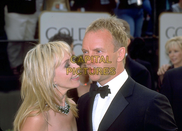 STING & TRUDI STYLER.Golden Globe Awards 2001 .Ref: 10304.celeb couple, blowing, bow tie, headshot, portrait.www.capitalpictures.com.sales@capitalpictures.com.©Capital Pictures
