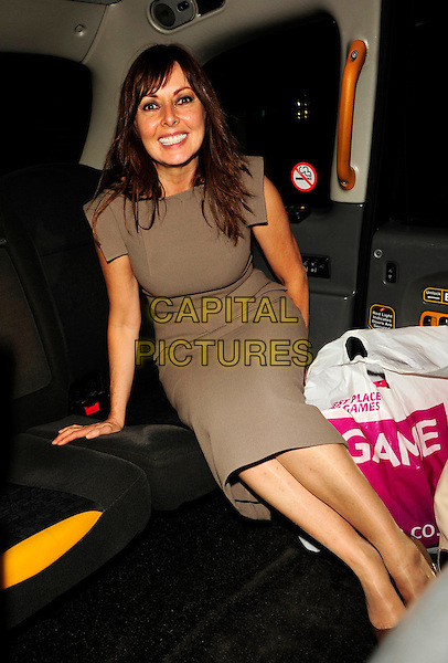 CAROL VORDERMAN.Spotted at The Ivy restaurant, London, England, August 13th 2008..half length sitting in car cab taxi car brown grey dress .CAP/CAN.©Can Nguyen/Capital Pictures