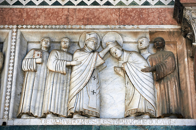 Late medieval relief sculpture of St Martin becoming a monk on the Facade of the Cattedrale di San Martino,  Duomo of Lucca, Tunscany, Italy,