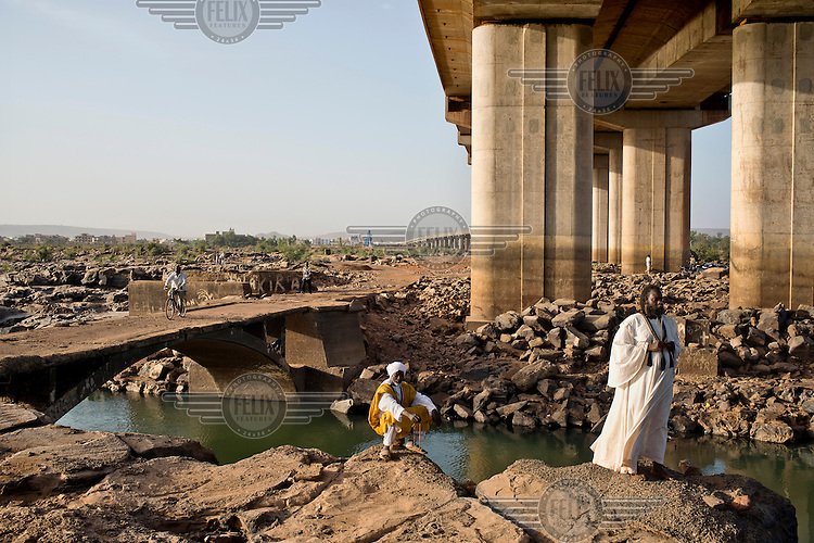 People beneath a Chinese built bridge spanning the River Niger. The bridge was opened in September 2011 and is the third crossing of the Niger in Bamako.