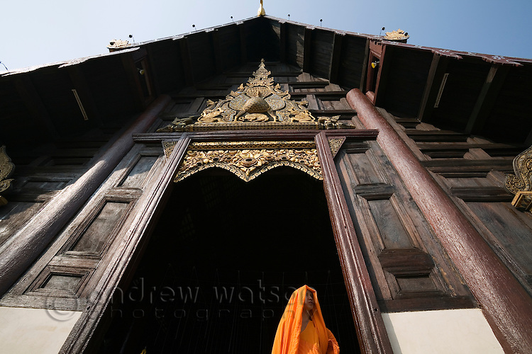 A monk stands in the towering entrance to Wat Phan Tao in Chiang Mai.  The Wat is constructed of teak panels and supported by 28 teak pillars.  Chiang Mai, Chiang Mai, THAILAND